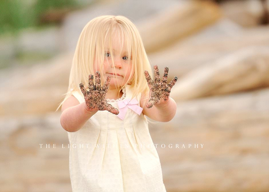 adorable little girl with sandy hands, beach photographer in Victoria BC