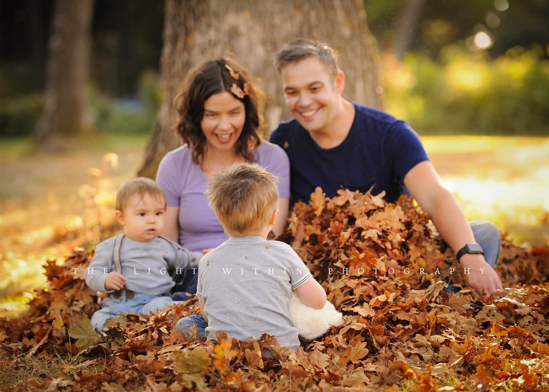 family sitting in a leaf pile under a tree, Victoria photographers
